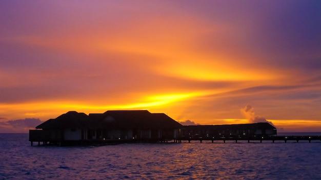Incroyable coucher de soleil avec paysage marin et villas sur l'eau aux maldives.