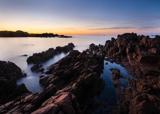 Incroyable coup d'une plage rocheuse au coucher du soleil