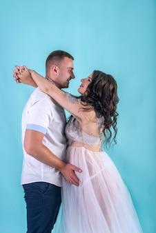Incroyable couple enceinte posant en studio sur fond bleu profond, attendant un bébé