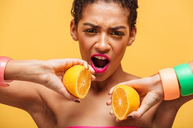 Incroyable femme afro-américaine conceptuelle mettant deux parties d'orange mûre de nouveau ensemble sur l'appareil photo isolé, sur le mur jaune