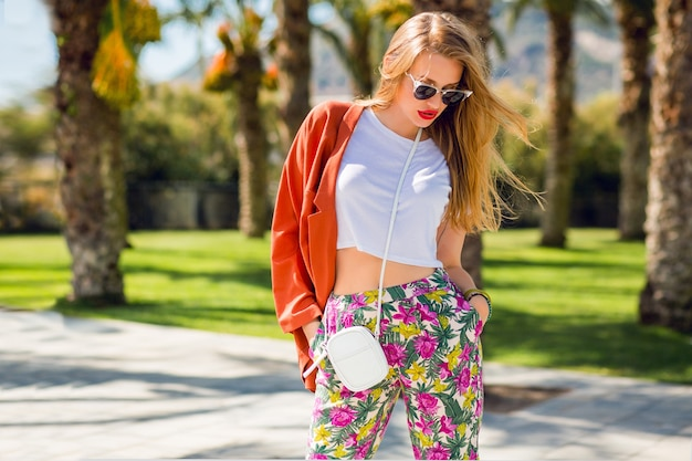Incroyable femme blonde en tenue d'été à la mode posant à l'extérieur