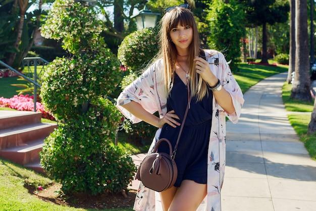 Incroyable femme élégante en combishort bleu et kimono blanc en vacances.