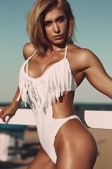 Incroyable femme sexy en maillot de bain blanc avec un corps de sport parfait posant à la plage. concept de corps de femme sport en maillot de bain