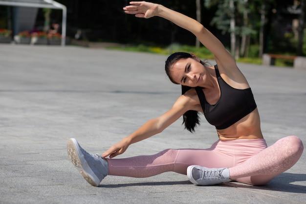 Incroyable fille athlétique bronzée portant des vêtements de sport faisant des exercices d'étirement dans le parc. espace pour le texte