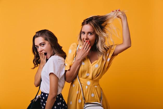 Incroyable fille aux cheveux bruns exprimant des émotions surprises tout en posant avec son meilleur ami. femme blonde caucasienne s'amusant avec sa sœur pendant la séance de portraits.