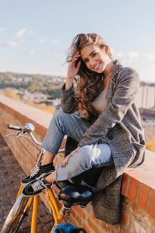 Incroyable fille aux cheveux bruns en pantalon en denim bleu assis sur fond de ciel en matinée ensoleillée