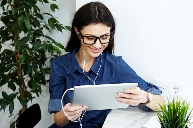 Incroyable fille aux cheveux noirs portant chemise bleue dépouillée et lunettes assis dans un café avec tablette et tasse de café, concept indépendant, portrait, écouter de la musique, souriant