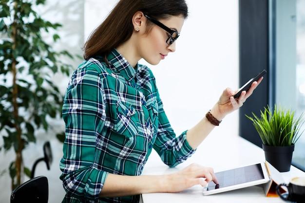 Incroyable fille aux cheveux noirs portant chemise et lunettes assis dans un café avec tablette et tasse de café, tenant un téléphone mobile, concept indépendant.