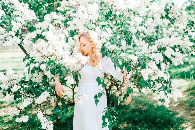 Incroyable jeune blonde joyeuse cendrillon modèle fille portrait. expressions du visage. l'été arrive. jolie femme dans des buissons de lilas en fleurs. fleur de jardin nature fabuleuse.