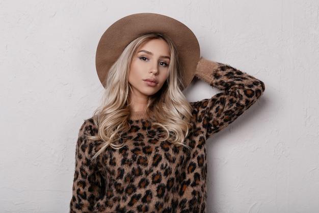 Incroyable jeune femme blonde glamour dans un chapeau beige à la mode dans un élégant pull léopard aux cheveux bouclés avec un beau maquillage naturel avec des lèvres sexy posant