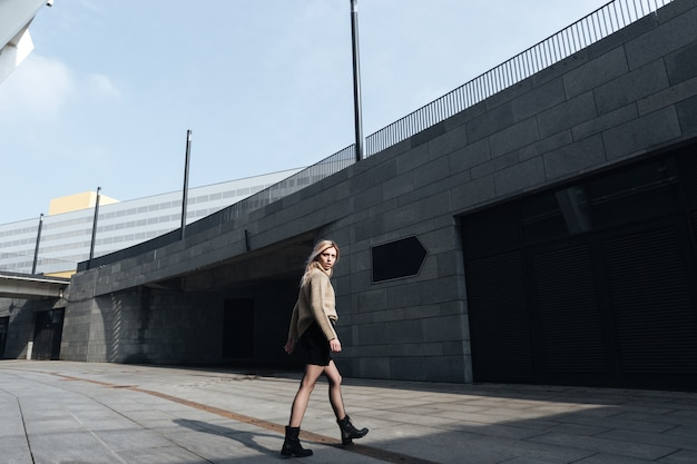 Incroyable jeune femme blonde marchant à l'extérieur. en regardant de côté.