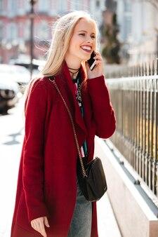 Incroyable jeune femme blonde de mode parler par téléphone.
