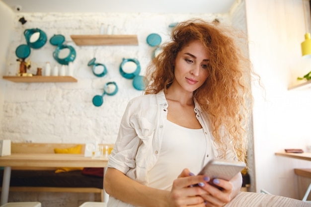 Incroyable jeune femme rousse assise dans un café tout en discutant