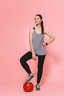 Incroyable jeune jolie femme fitness posant avec ballon isolé sur mur rose