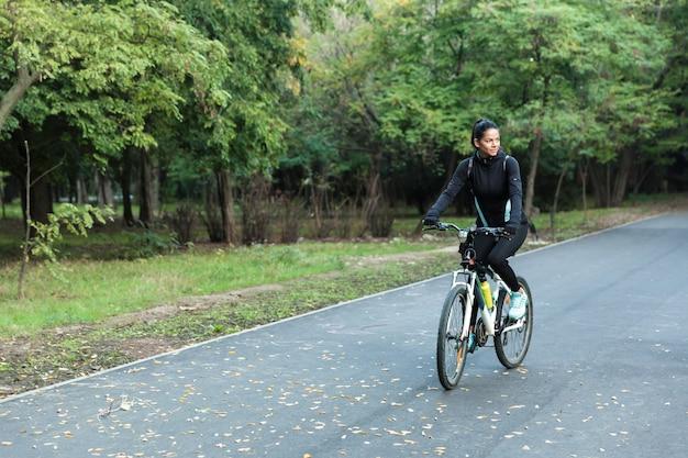 Incroyable jolie femme marchant à vélo dans le parc à l'extérieur.