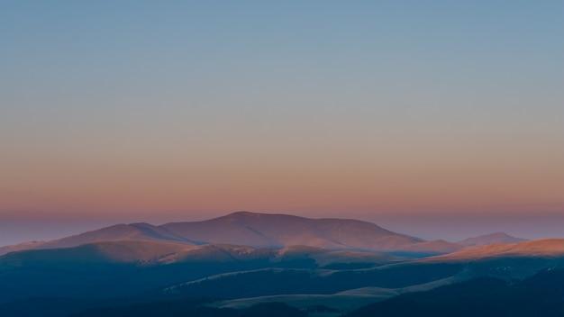 Incroyable lever de soleil d'été avec de belles lumières orange sur les montagnes du sommet, le parc bucegi au lever du soleil, les montagnes des carpates. lumière du lever du soleil