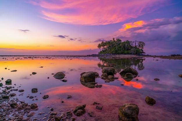 Incroyable lumière coucher de soleil ciel sur petite île en mer tropicale coucher de soleil ou heure du lever du soleil à marée basse jour avec des rochers au premier plan beau paysage naturel paysage marin.
