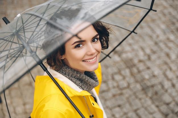 Incroyable portrait de jeune femme en manteau jaune debout sous un parapluie transparent avec un large sourire sincère