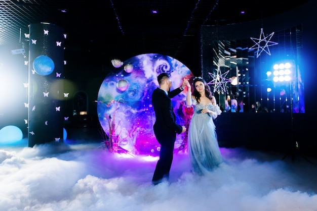 Incroyable première danse de mariage sur une fumée épaisse avec une belle lumière et athos. décor dans le style de l'espace. mariage dans l'espace