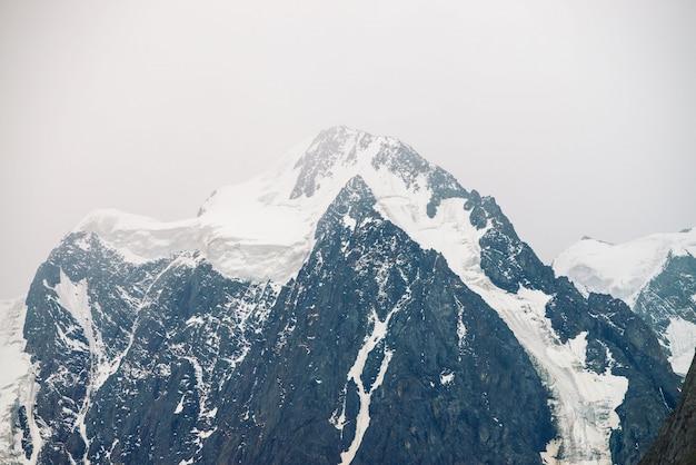 Incroyable sommet du glacier. chaîne de montagnes enneigée dans un ciel couvert.