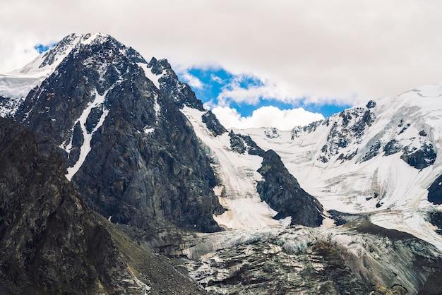 Incroyable sommet du glacier. chaîne de montagnes enneigées dans le ciel bleu nuageux.