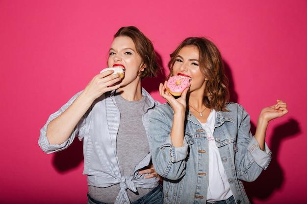 Incroyables deux amies mangeant des beignets