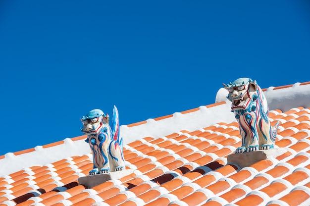 Incroyables deux statues shisa très colorées, hommes et femmes, utilisées comme protection sur le toit rouge