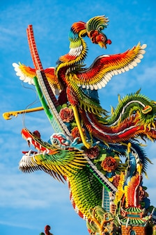 Incroyables figurines chinoises colorées de dragon et phoenix l'une sur l'autre éclairées par la lumière du soleil