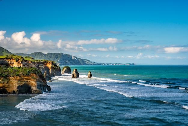 Incroyables formations rocheuses les trois sœurs sur la plage de tongaporutu bordée d'immenses falaises et de la montagne volcanique
