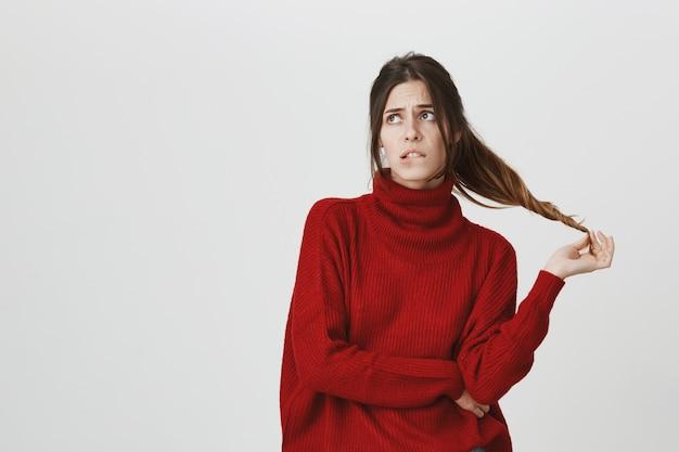 Indécis et perplexe jeune femme stupide pensant, mordre la lèvre