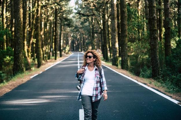 Indépendance voyageur solitaire caucasien heureux femme joyeuse avec sac à dos marchant au milieu d'une belle forêt de hauts arbres