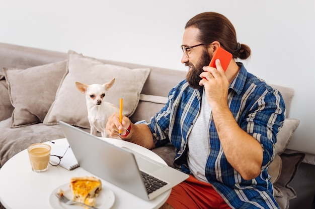 Indépendant barbu aux cheveux noirs portant une chemise bleue carrée se sentant occupé à travailler à domicile