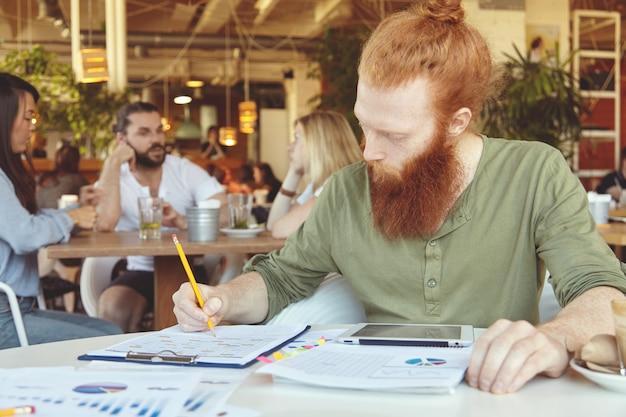 Indépendant hipster tenant un crayon, prenant des notes sur des feuilles de papier avec des graphiques, utilisant une tablette numérique pour un travail à distance dans un espace de travail partagé.