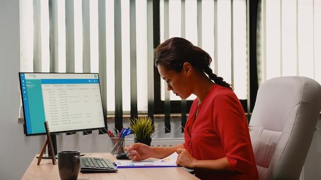 Indépendant hispanique travaillant à l'aide d'un presse-papiers et d'un ordinateur sur son lieu de travail tôt le matin. entrepreneur assis sur une chaise dans l'espace de travail d'une entreprise professionnelle en tapant sur le clavier de l'ordinateur en regardant le bureau