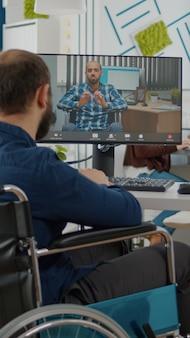 Indépendant immobilisé invalide paralysé parlant en vidéoconférence avec un collègue handicapé à distance discutant en ligne assis devant un ordinateur en fauteuil roulant. bureau de démarrage pendant la réunion virtuelle
