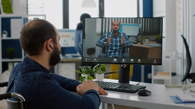 Indépendant invalide parlant en visioconférence avec un collègue à distance
