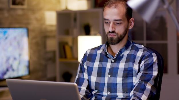 Indépendant masculin tapant sur un ordinateur portable pendant les heures de nuit dans son bureau à domicile.