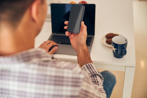 Indépendant masculin utilisant ses gadgets au petit déjeuner