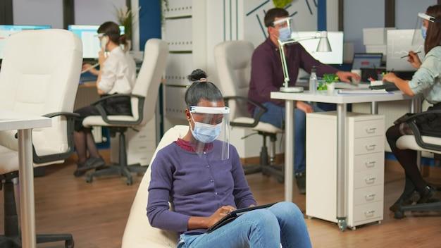 Indépendant noir avec masque de protection contre le coronavirus assis sur un pouf au milieu d'une salle de bureau analysant le projet sur tablette numérique. équipe commerciale multiethnique travaillant dans le respect de la distance sociale