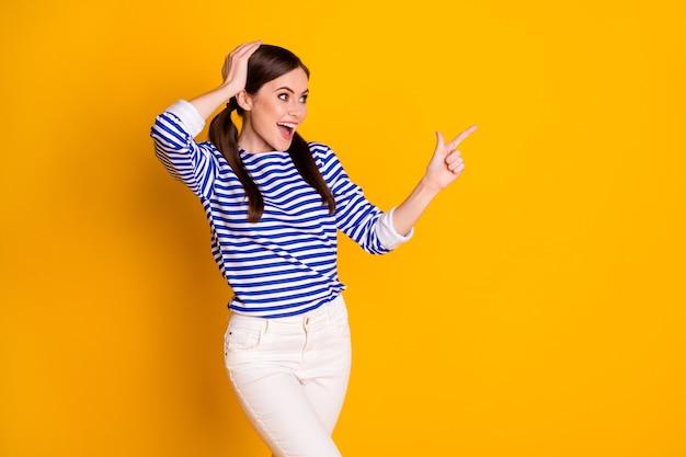 L'index de l'index du promoteur surpris d'une fille folle indique une promotion d'annonces incroyable de manière directe, portez une tenue de bonne apparence isolée sur fond de couleur brillante