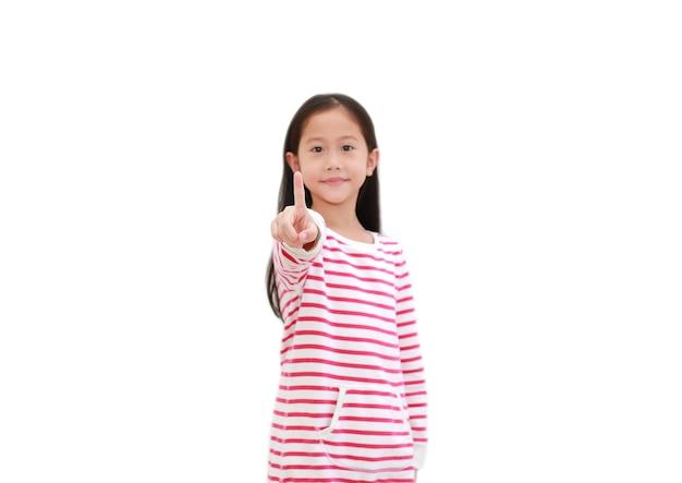 L'index de point de l'enfant asiatique en appuyant sur un bouton imaginaire à l'avant isolé