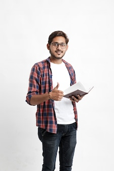Indian college student holding cartable et montrant carnet de notes sur un mur blanc
