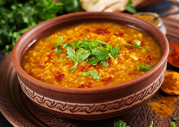 Indian dhal curry épicé dans un bol, épices, herbes, table en bois noir rustique.