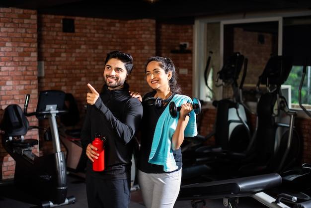 Indien asiatique jeune couple travaille dans la salle de gym. une femme séduisante et un bel homme en forme s'entraînent dans une salle de sport moderne - concept de santé et de remise en forme