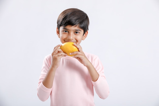 Indien / asiatique petit garçon mangeant de la mangue