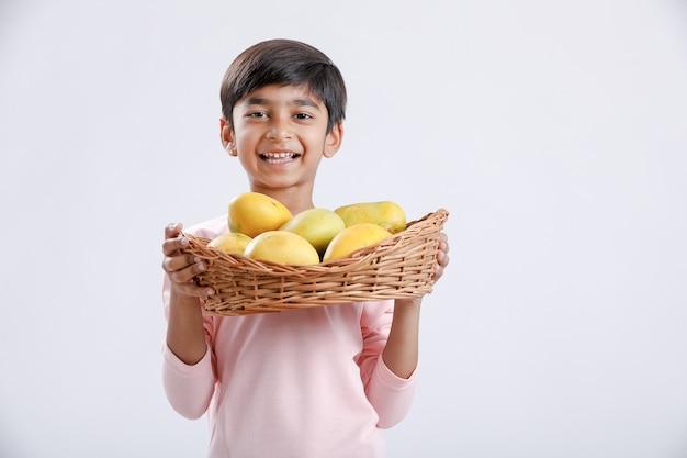 Indien / asiatique petit garçon tenant un panier de mangue à la main