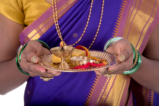 Indien, femme, exécuter, adoration, portrait, de, a, beau, jeune femme, à, pooja, thali, isolé, blanc, mur