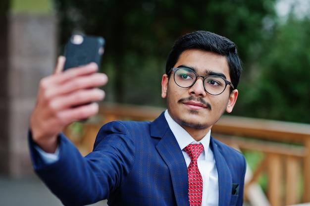 Indien jeune homme à lunettes, porter sur costume avec cravate rouge posé en plein air et faire selfie sur téléphone mobile.