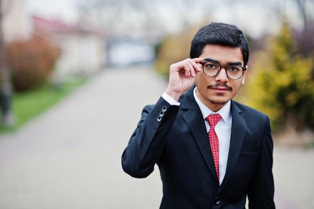 Indien jeune homme à lunettes, porter sur costume avec cravate rouge posé en plein air.