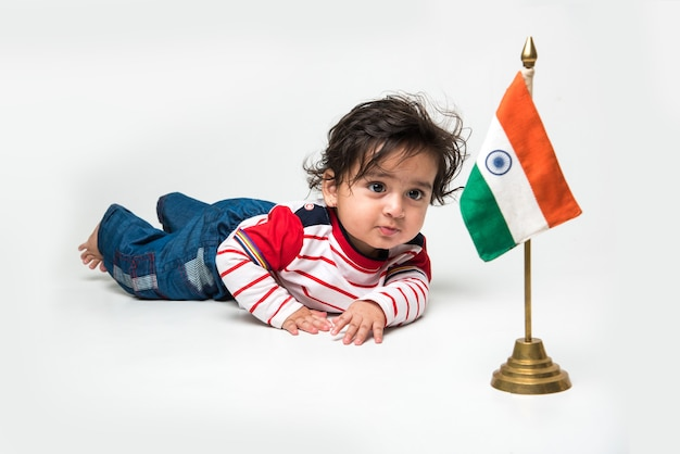 Indien mignon petit bébé garçon ou nourrisson ou enfant en bas âge avec drapeau tricolore indien, isolé sur fond blanc